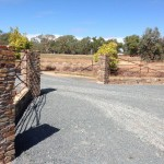 Driveway entrance of sandstone pillars framing rustic iron gates